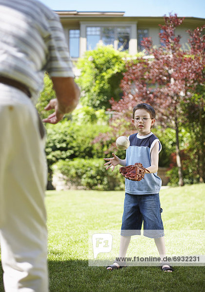 Man Playing Catch with Boy