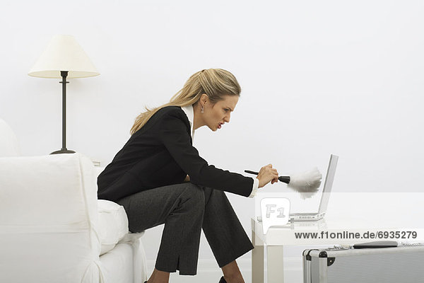 Businesswoman Dusting Laptop