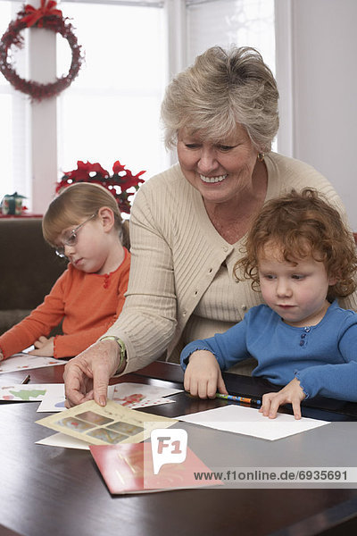 Woman Writing Christmas Cards with Grandchildren