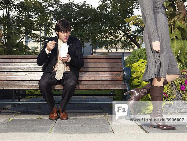 Frau  Mann  sehen  gehen  Sitzbank  Bank  essen  essend  isst  Mittagessen
