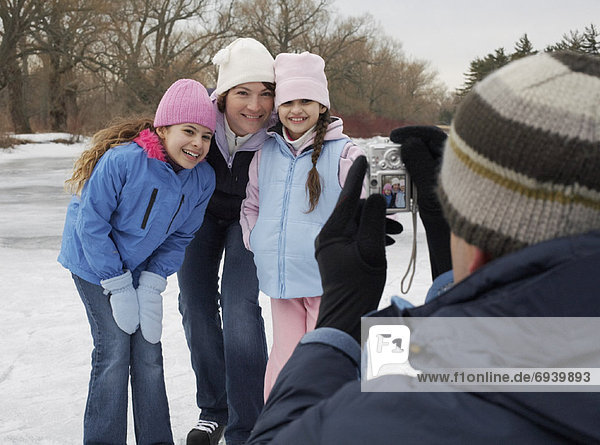 Father Taking Picture of Family Skating