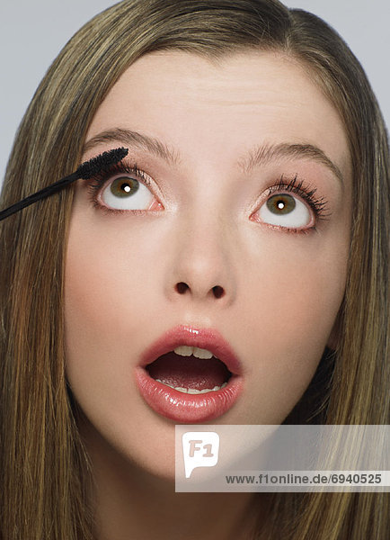 Young Woman Putting on Mascara