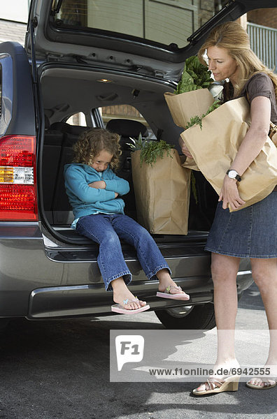 Mother with Daughter  Removing Groceries from Car