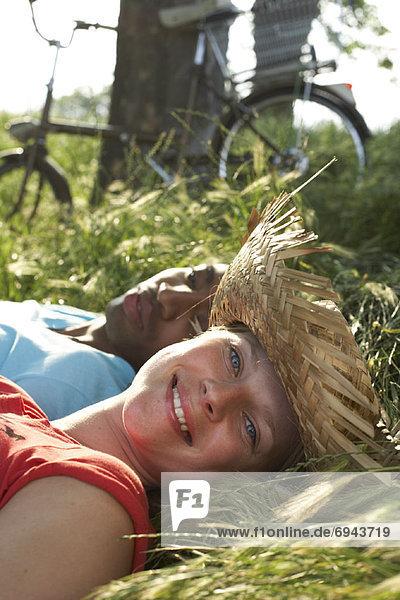 Paar im Gras liegend