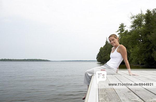 Frau sitzt auf Dock