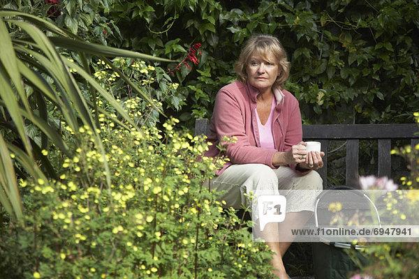 Frau sitzt im Garten