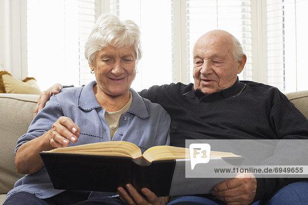 sitzend Senior Senioren Zusammenhalt sehen Couch Buch Taschenbuch