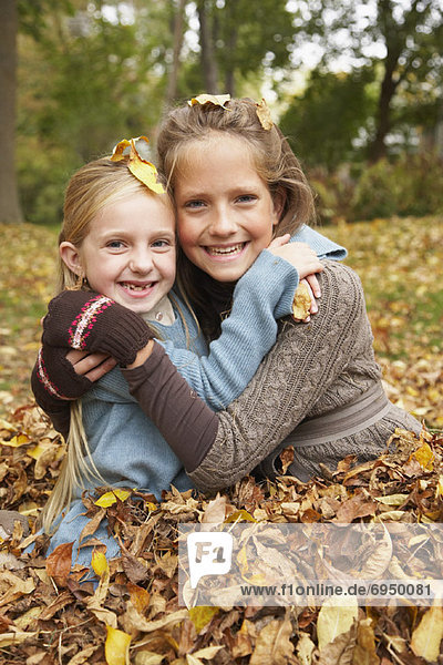 Portrait of Girls Sitting in Autumn Leaves