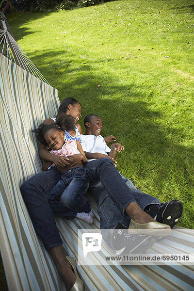Mother with Son and Daughter in Hammock