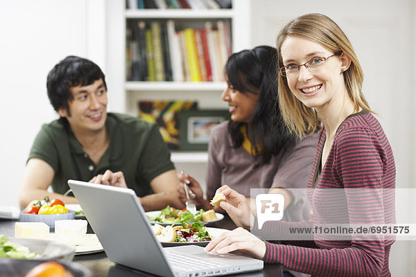 Woman Using Laptop Computer at the Dinner Table