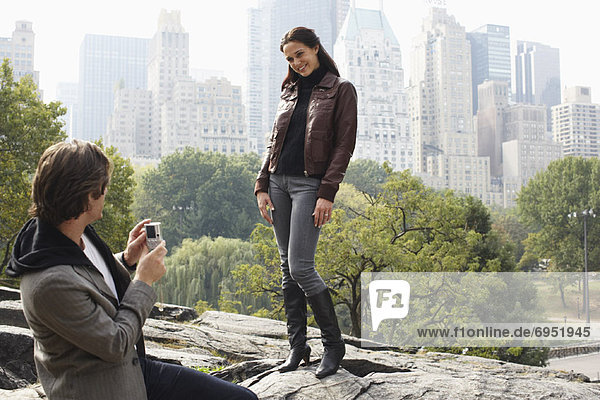 Man Taking Womans Picture in City Park  New York City  New York  USA