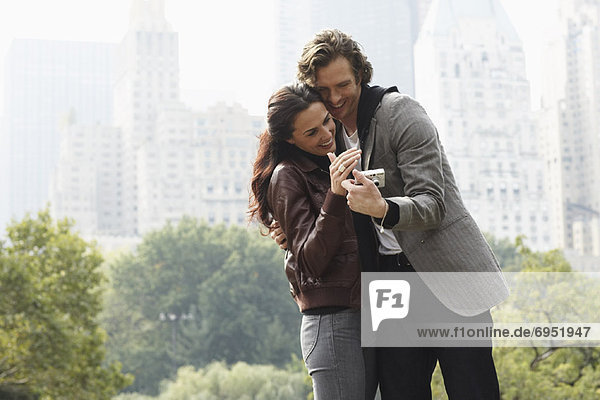 Couple Looking at Digital Camera in City Park  New York City  New York  USA