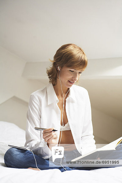 Woman on Bed with Mp3 Player and Journal