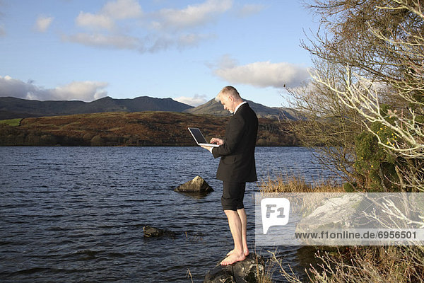 Businessman with Laptop Computer by Lake Windermere  Cumbria  England