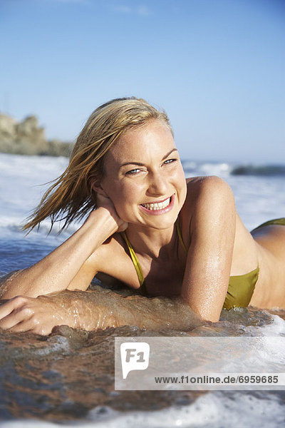 Close-up Portrait of Woman Lying in the Water at Beach