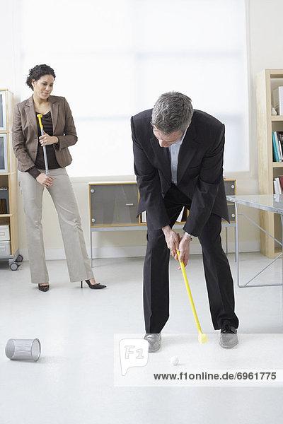 Geschäftsfrau  Geschäftsmann  Büro  Golfsport  Golf  spielen