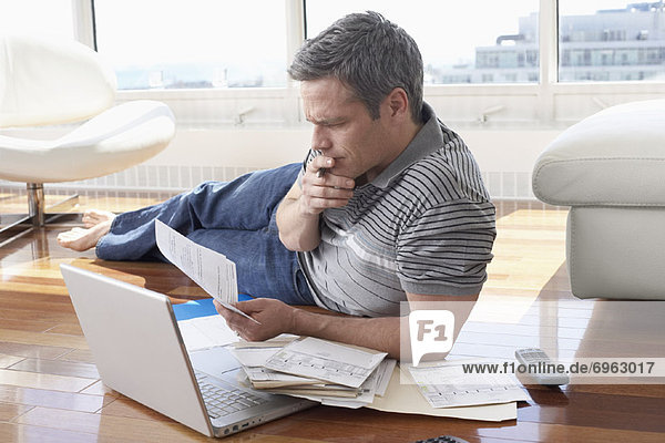 Man with Bills and Laptop Computer