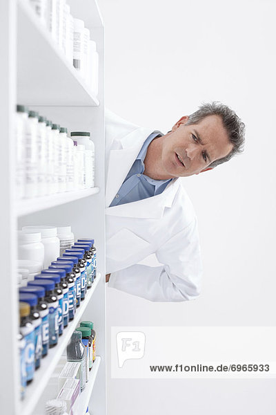 Pharmacist Looking at Pills on Shelf