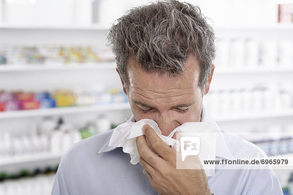 Man in Pharmacy Blowing Nose