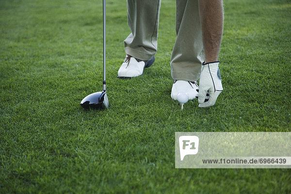 Golfer platzieren Ball auf Tee