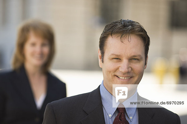 Portrait of Businessman Outdoors  Businesswoman in the Background