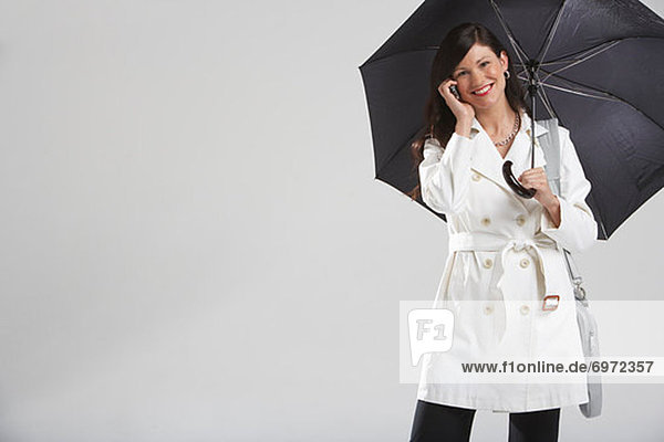 Portrait of Businesswoman Holding Umbrella and Talking on Cell Phone