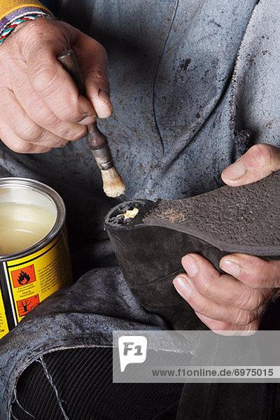 Close-up of Italian Shoemaker Applying Glue to Heel of Boot
