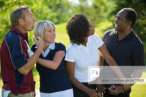 Couples Chatting on Golf Course