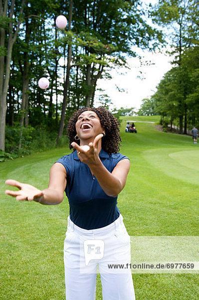 Woman Juggling Golf Balls on Golf Course