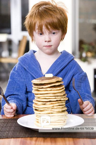 Stapel  Junge - Person  klein  essen  essend  isst  Pfannkuchen  Felssäule