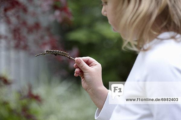 Girl Holding a Caterpillar on a Stick