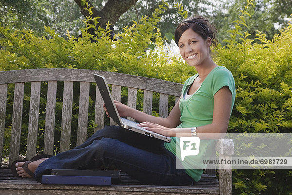 University Student Sitting on a Bench Using a Laptop Computer