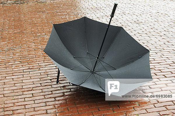 Kopfsteinpflaster  liegend  liegen  liegt  liegendes  liegender  liegende  daliegen  Regenschirm  Schirm  nass  offen