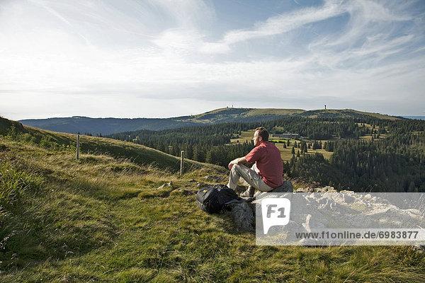 Single hiker on Mt Herzogenhorn enjoying the view to Mt Feldberg in the Black Forest  Baden-Wuerttemberg  Germany  Europe