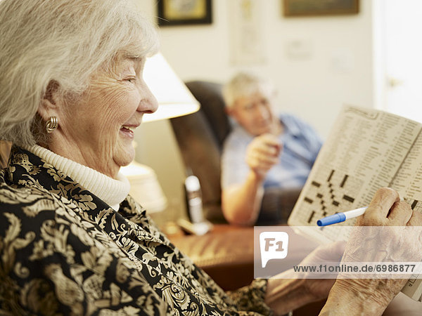 Elderly Couple in Retirement Home  Woman Working on Crossword Puzzle