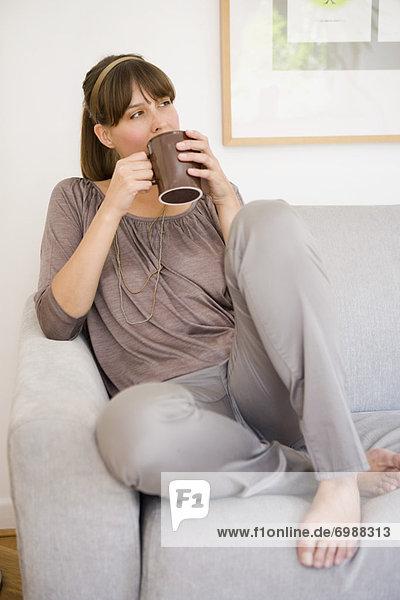 sitzend  Frau  Tasse  Couch  halten