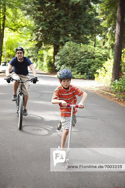 Vereinigte Staaten von Amerika USA Junge - Person Menschlicher Vater folgen Fahrrad Rad
