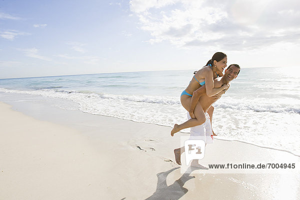 Frau Mann geben Strand fahren huckepack mitfahren