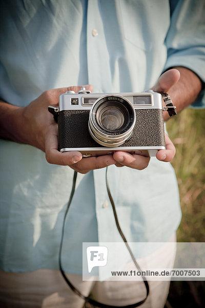 Close-up of Man holding Vintage Camera