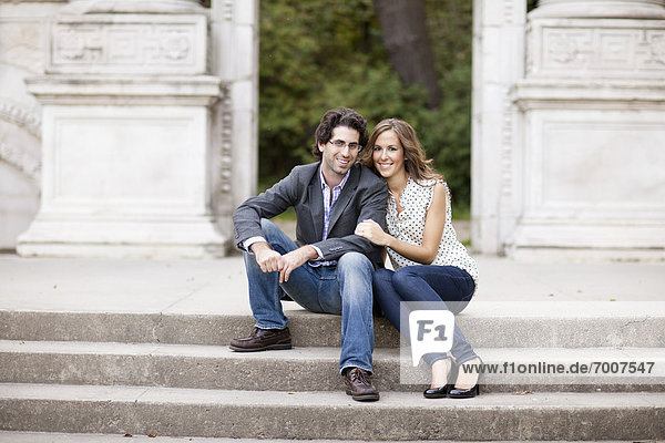 Portrait of Young Couple Sitting on Stairs in Park  Ontario  Canada