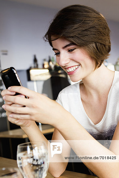 Businesswoman using cell phone in cafe
