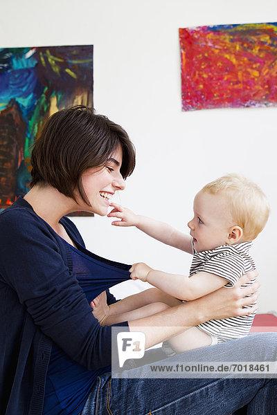Mutter spielt mit Baby im Wohnzimmer