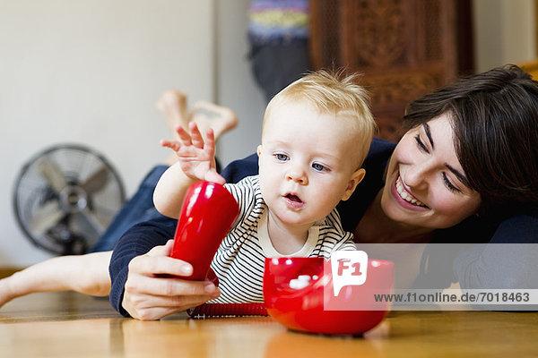 Mutter und Baby spielen auf dem Boden