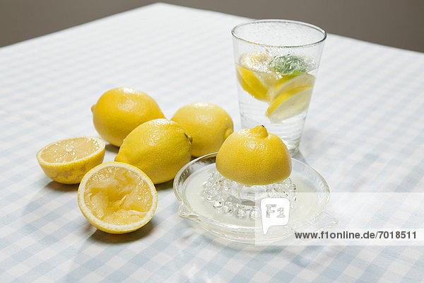 Zitronen  Saftpresse und Glas Wasser