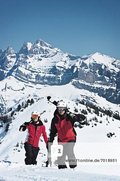 Skifahrer klettern auf verschneite Berghänge