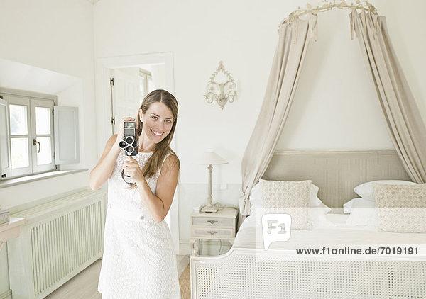 Frau mit Videokamera im Schlafzimmer