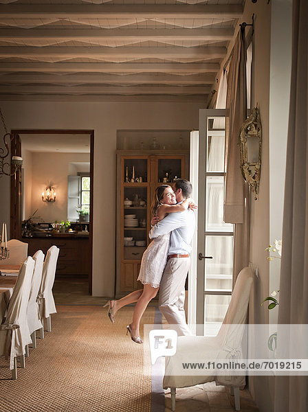 Couple hugging in dining room
