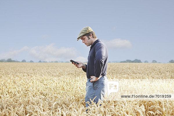 Landwirt mit Handy im Ackerbau Landwirt mit Handy im Ackerbau