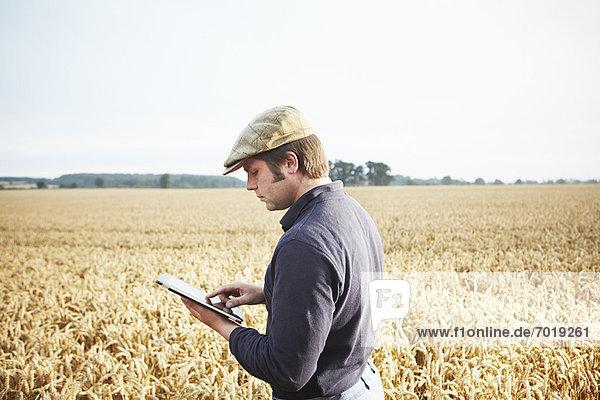 Landwirt mit Tablet-Computer im Feld Landwirt mit Tablet-Computer im Feld