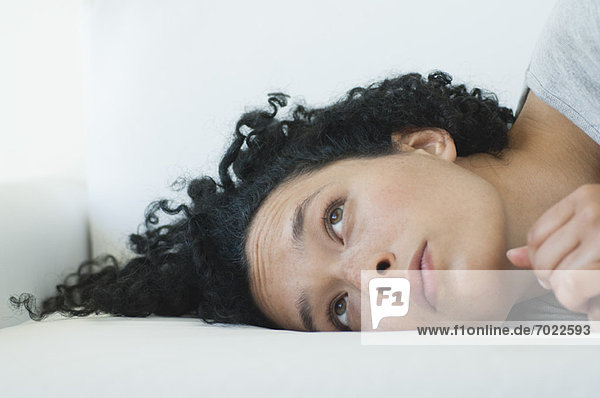 Young woman lying on side  idly looking up